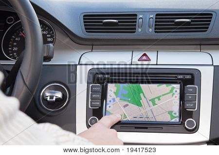 GPS navigation panel on dashboard inside a car. Finger pointing on destination point.