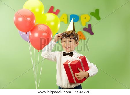 Portrait of happy lad with giftbox putting off funny eyeglasses on birthday party