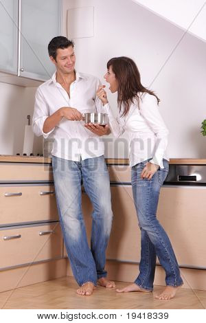 Young couple in the kitchen feeding with soup