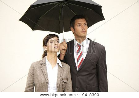 Business team of man and woman with umbrella