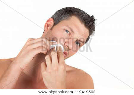 Man in bathroom cleaning face skin with batting pads