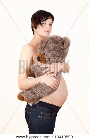 Pregnant woman holding teddy on stomach
