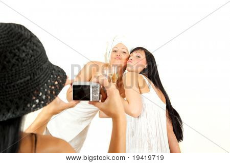Group of three beautiful attractive girls having fun while taking picture. blond girl is pampered in towel and brunette in dress. both drinking champagne and smiling to camera of third girl