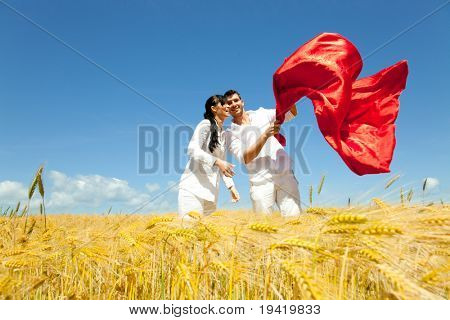 Playful confident couple of mid adult man and woman standing in yellow corn field together embracing in casual clothes and throwing a red big scarf