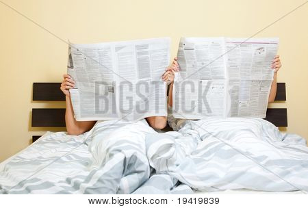 Pair of two lying in bed and reading newspaper like every weekend morning