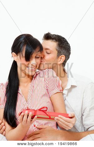 Happy loving couple giving present gift while embracing and kissing