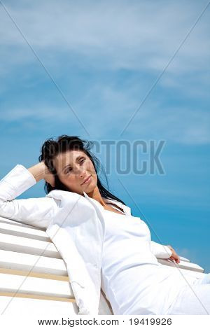 Successful confident business woman sitting on white bank with blue background sky