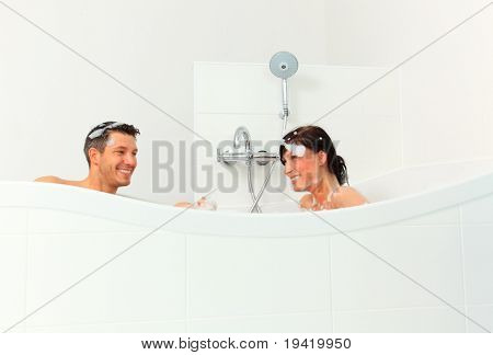 Woman and man at home taking a bath with a lot of foam in tub and shower
