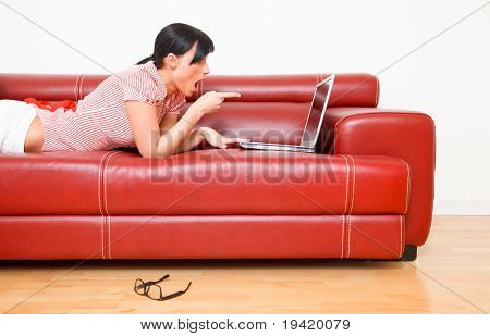 Happy surprised internet brwosing woman showing finger thumb to laptop screen while lying at home on red couch