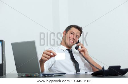 Phoning desk sitting businessman holding blank businesscard with smiling