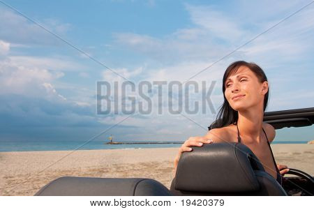 Cabriolet woman parking on the beach with ocean sea and coastline in background