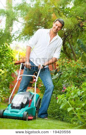Man cutting green grass at home in tropical garden