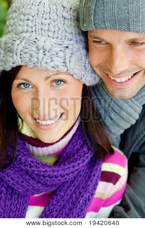 Embracing romantic couple in cold weather time with warm clothes cap and scarf