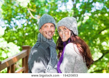 Happy natural walking couple in forest park wearing winter clothes