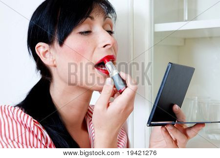 Woman putting on red lipstick make-up at home in bath