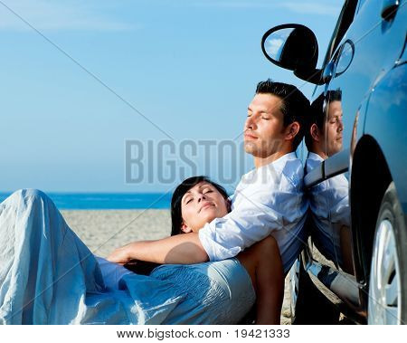 Couple relaxing on car on the beach