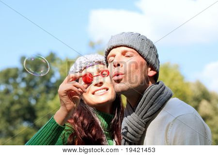 Fun having couple making soap bubbles in forest