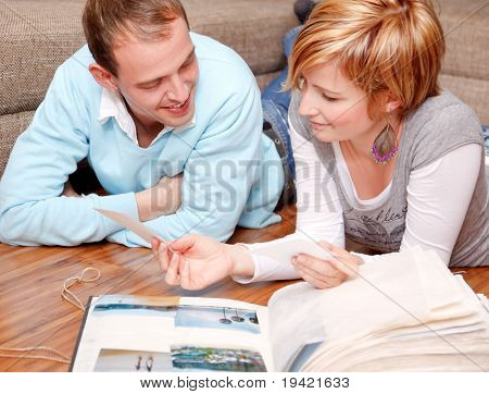 Scenic of talking pair couple at home in domestic room lying on floor looking at photo album from last family travel vacation journey