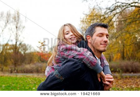 Fun having embracing active family of father with child walking outdoors on weekend in forest park in autumn fall day enjoying the time together