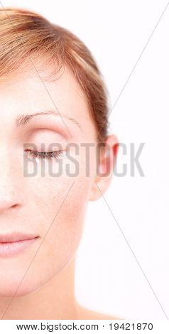 Female face with cosmetic cream points under eyes for rejuvenation appearance