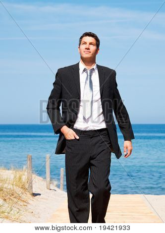 Carefree successful businessman walking with success on boardwalk on coastline with blue sky and sea wearing tie and formal clothes