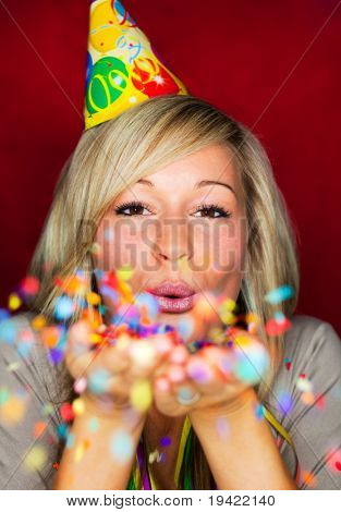 Cheerful lifestyle party celebrating girl with blowing confetti to camera