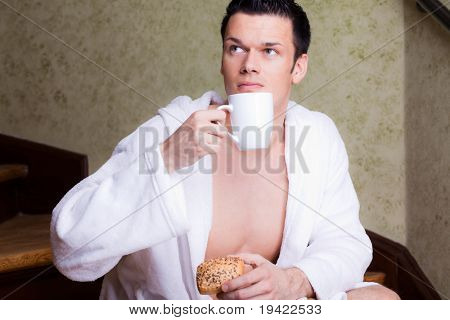 Breakfast enjoying man with newspaper and cup