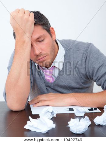 Bored businessman blowing papers on table