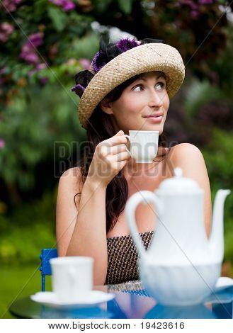 nostalgic beauty sitting on table in garden drinking tea