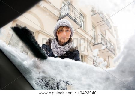 person removing snow and ice from window