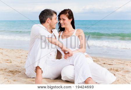 Amor pareja sentada en la playa