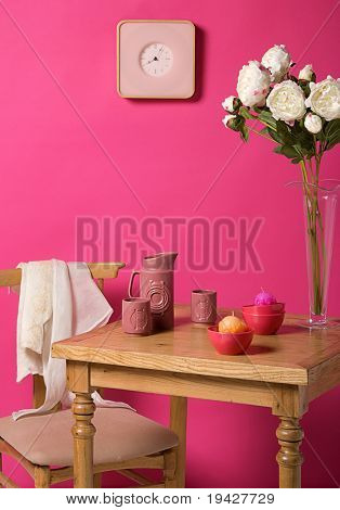 table and a chair in the front of a pink wall