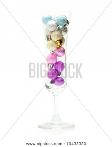 Christmas ornaments in a Champagne glass.  Christmas ball ornaments stacked in a champagne glass isolated on white. Concept image for holiday season events and partys.