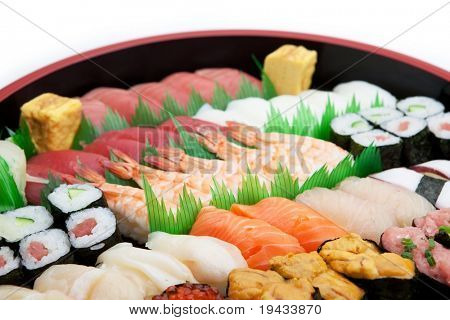 Sushi arranged in a traditional sushi tray. isolated on white.