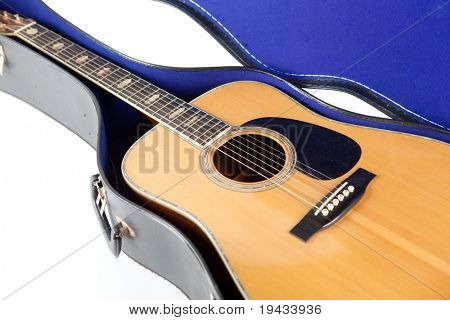 Steel string acoustic guitar, inside an open case. isolated on white.