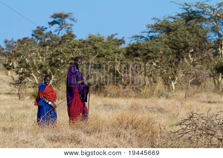 SERENGETI, TANZANIA - JUNE 6: Unidentified Masai Warriors walk in the Africa bush to protect  cattle on June 6, 2010 in the Serengeti, Tanzania.