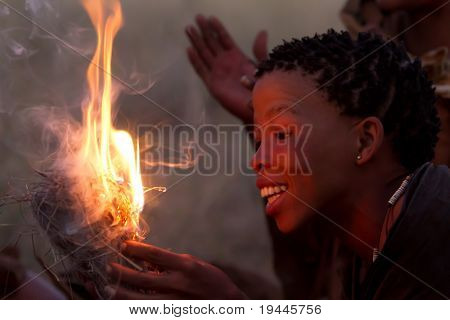 SERENGETI, TANZANIA - JUNE 6: Unidentified Bushman women making fire on June 6, 2010 in the Serengeti, Tanzania.