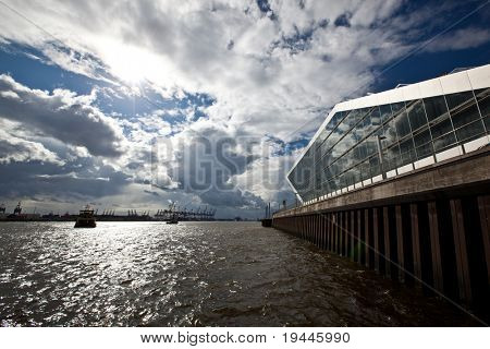HAMBURG, GERMANY - AUGUST 28: Hamburg Dockland - modern Building in the habor. In the background are cargo ships. August 28, 2010 in Hamburg, Germany.