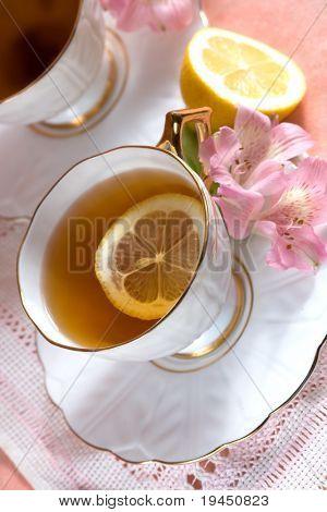 con sabor a té en un recipiente de porcelana blanca y una flor