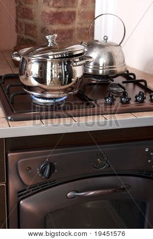 Metal cooking pan on gas burner with burning gas flames