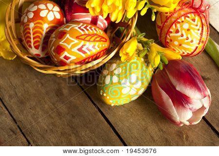 Basket full of Easter eggs and tilips
