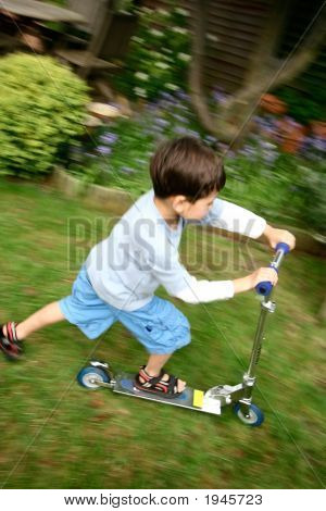 Young Boy Having Fun Riding On His Scooter