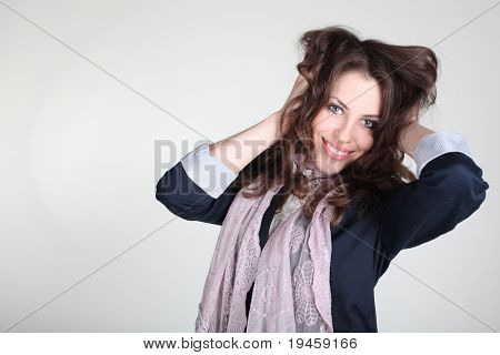 Brunette girl touching hair over gray background. Studio shot with copy-space.