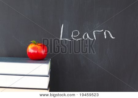 "Stack of books with a red apple and a blackboard with ""learn"" written on it"