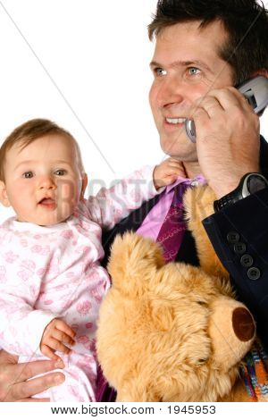 Businessman On Phone While Holding Baby