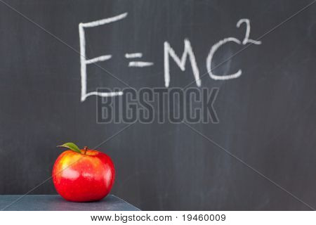 Stack of books with a red apple and a blackboard with a formula written on it