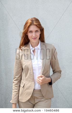 Smiling businesswoman standing in front of wall