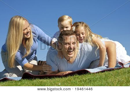 An attractive, young family of four playing together at the park
