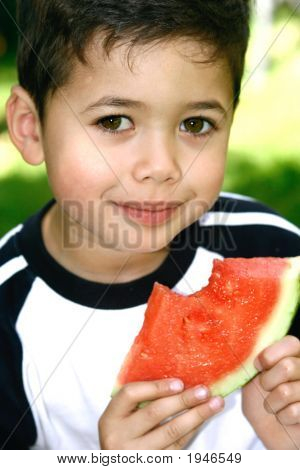 Young Boy Enjoying Juicy Watermelon In Park