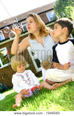 Family In Garden Blowing Bubbles